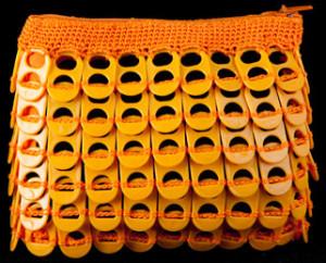 Monedero confeccionado con anillas de lata de plástico de color naranja.