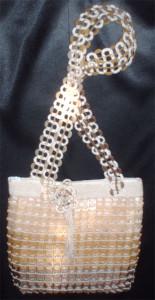 Bolso hecho con anillas de lata de plástico en colores marfil, oro claro y oro viejo.